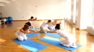 People doing yoga exercise with instructor.