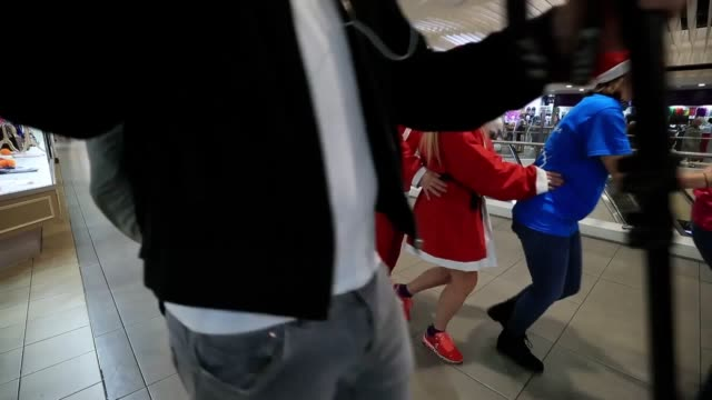 People dressed as Santa perform the conga in St Johns Shopping Centre in Liverpool during the launch of the 14th annual Liverpool Santa Dash