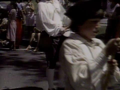 People dressed in 18th century costumes march through the town of Havard and fire rifles to celebrate American Independence Day 4 July 1983