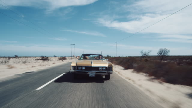 People driving in retro car on outback road