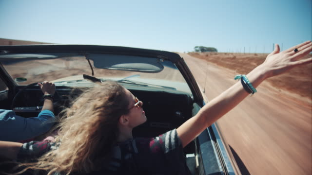 People driving in retro car over dirt road
