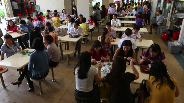 People eat lunch at the Amoy Street Hawker Market on February 22 2013 in Singapore Hawker markets are open air complexes of inexpensive cooked food...