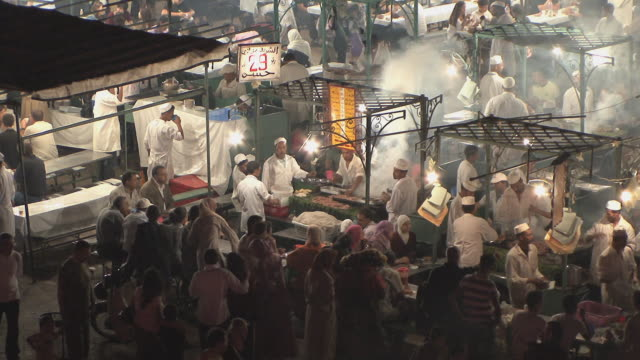 MS HA People eating at food stalls in overcrowded Djemaa el Fna square, Marrakech, Morocco