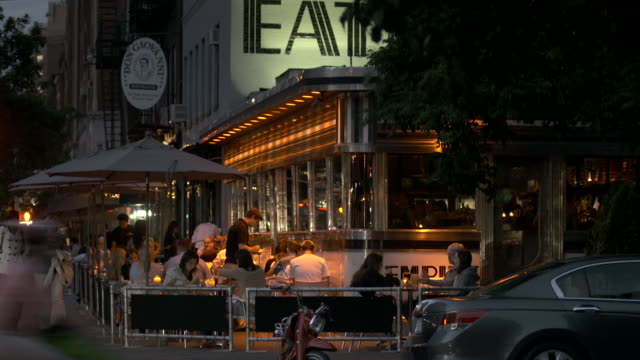 People eating outside in the evening at the Famous Empire Diner, the Eat sign is displayed at the top of the frame.