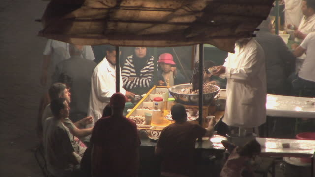 MS HA People eating snails at street stall, Djemaa el Fna square, Marrakech, Morocco
