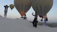 People enjoy hot air ballooning over the famous volcanic rock formations in Cappadocia on the first day of threeday Eid alFitr festival marking the...