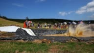 People enjoy the muddy thrills and spills on a waterslide dug into a hillside in Waimauku on February 23 2013 in Auckland New Zealand Only 2000...
