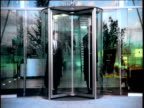 People entering and leaving modern office building via revolving doors London