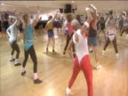 People exercising in aerobics studio wearing leotards leg warmers and eighties style sports wear