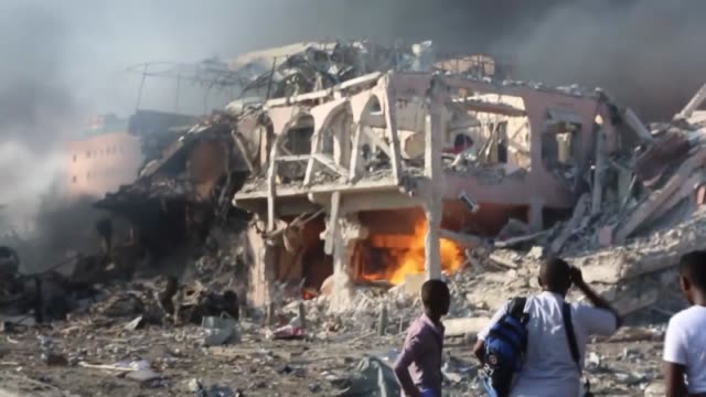 People gather at the site of a blast in Mogadishu Somalia on October 14 2017 Over 20 people were killed more than 18 others wounded when a truck full...