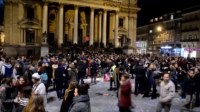 People gather in front of the Place de la Bourse during a vigil to pay tribute to the victims of the terrorists attacks in Brussels Belgium on March...