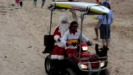 People gather to watch as Santa Claus arrives at Sydneys Dee Why Beach to greet children in the lead up to Christmas on December 23 2012 CLEAN Santa...
