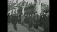 VS people gathered around the wrought iron fence at Parliament / three men wearing newsboy caps / VS Prime Minister Stanley Baldwin exits 10 Downing...