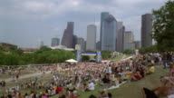 WS  TIME LAPSE people gathering on lawn for outdoor concert  cityscape in background   Houston  Texas  USA