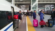 People get off the highspeed bullet train at Hefei Railway Station at the travel rush season as families gather to celebrate the forthcoming Chinese...