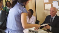 CU, People giving forms to resource representatives in unemployment office, Phoenix, Arizona, USA