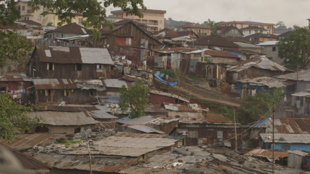People go about their daily lives on a hillside densely-occupied by improvised corrugated iron housing in Kenema, Sierra Leone.