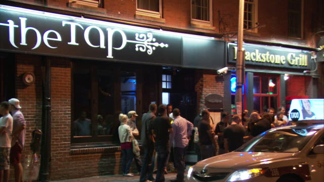 MS People hanging out on Union Street in front of bar at night / Boston, Massachusetts, USA