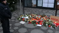 People have laid flowers for the victims of terror attacks a sign with the words 'Why' can be seen and a police officer is standing nearby On a...