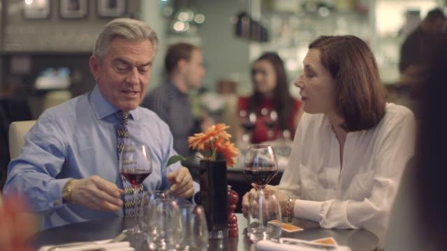 MS R/F People having food in restaurant, waiter serving food