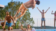 SLO MO DS People having fun at a pool party at sunset while cheering for their friend doing a back flip into the water