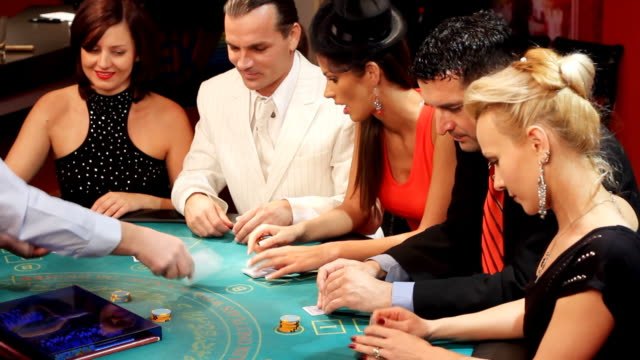 People having fun at the Blackjacks table in casino.