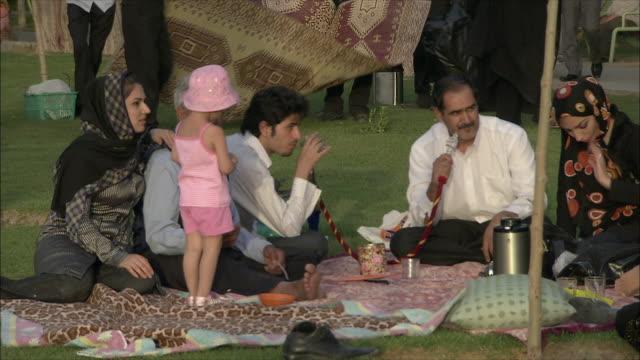 MS People having picnic on lawn, men smoking hookah pipe, Isfahan, Iran