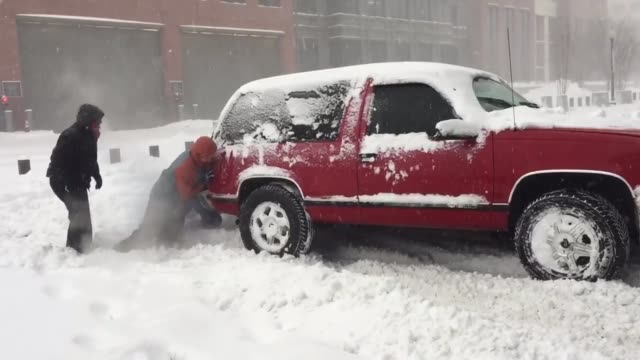 People help push an SUV stuck in the snow in Washington DC