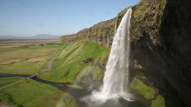 People hiking around tall waterfall near green fields in Iceland