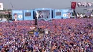 People hold a giant Turkish flag and poster of Turkey's Prime Minister leader of the ruling Justice and Development Party Ahmet Davutoglu as he...