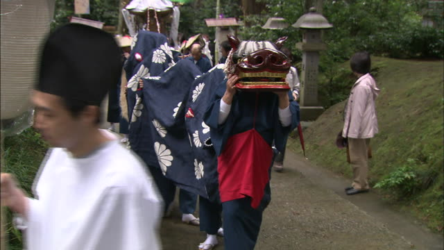 People in a traditional Asian lion costume walk up garden path in Takaoka, Japan.