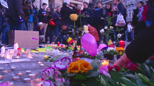 People in Belgium pay tribute to the victims of the Brussels terror attacks with candles and a miniature Belgian flag