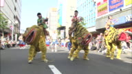 People in costumes perform the tiger dance during a parade.