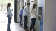 Leute in der Schlange warten auf Geld aus Geldautomaten abheben
