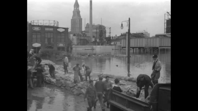 LS people in rowboats in flooded streets of New London / VS men unload sandbags work to pile them to form a levee / VS others pile sandbags to...