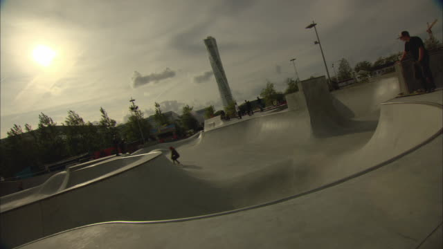 WS People in skate park with Turning Torso building in background / Malmo, Sweden
