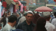 MS People in traditional Uighur clothing walking through market street / Kashgar, Xinjiang, China