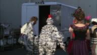 MS POV People in various costumes walking in film set
