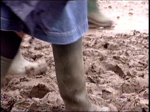 People in wellies stepping through mud at Glastonbury Festival; Jun 05