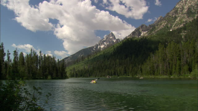 People kayak on a lake in Grand Teton National Park in Wyoming.