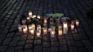 People leave candles and flowers in the town square in Turku Finland where a man went on a stabbing spree killing two people and wounding six others