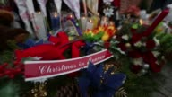 People leave flowers toys candles and notes to a memorial near Tompkins Ave and Myrtle Ave on December 21 2014 in New York near the site where two...