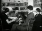 Two couples playing cards at table in den men in rural clothing sitting around pot belly stove MS Mail sacks being emptied of contents large bundles...