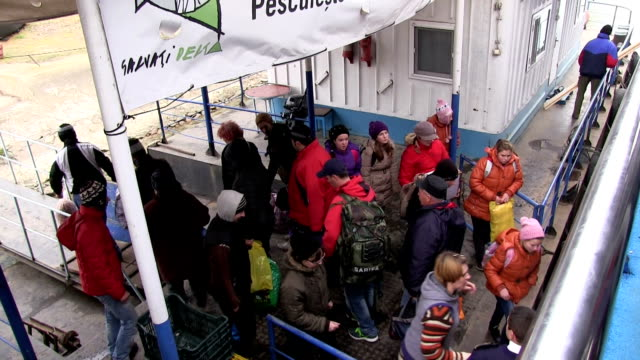 People loading and unloading from boat at dock, Romania, Danube river