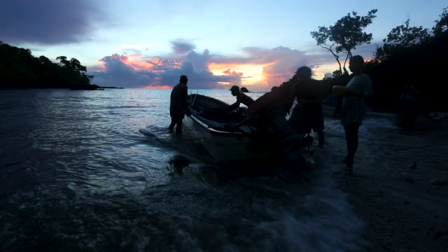 People loading up small motor boat on the coast at sunrise