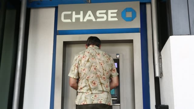 People make their way past Chase Bank branches in Miami FL on January 10 2016 Shots shot of glass window as person uses ATM inside tilt down to Chase...