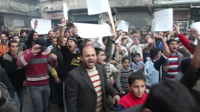 People march and yell during a protest outside a bakery in Aleppo Syria