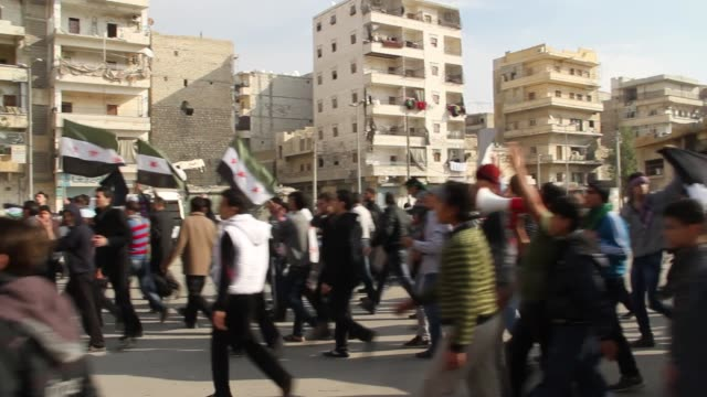 People march in the streets in protest of the Syrian Regime