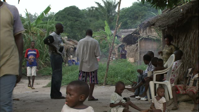 People mill about amongst straw huts in rural village on Niger Delta, Kura region, Nigeria