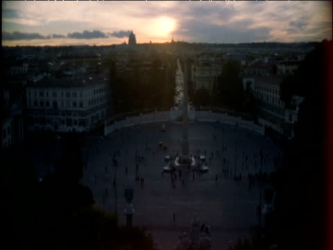 People mill about in St Peter's Square at dusk